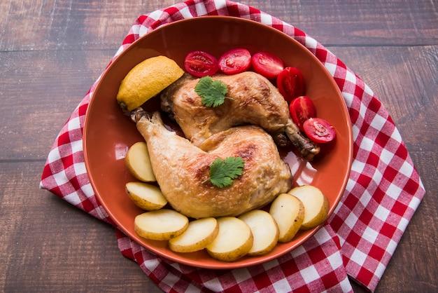 Расположение жареных куриных ножек с ломтиками помидоров и картофеля в миске над скатертью