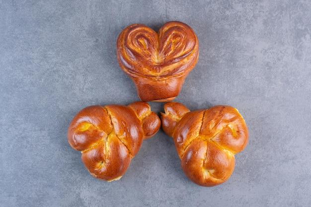 Композиция из булочек в форме сердца на мраморном фоне. фото высокого качества