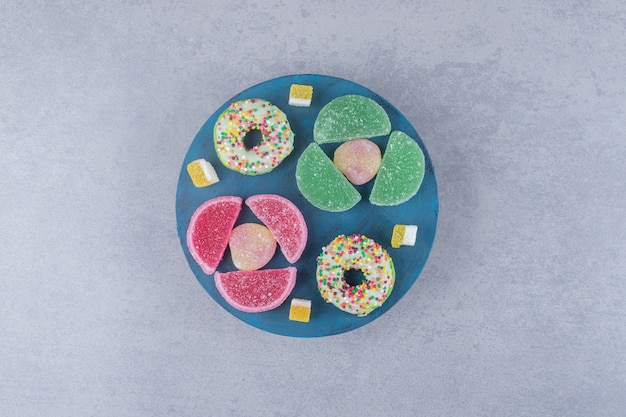 대리석 표면의 블루 보드에 marmelades와 도넛의 배열