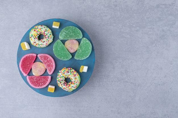 大理石の表面の青い板にマーマレードとドーナツを配置