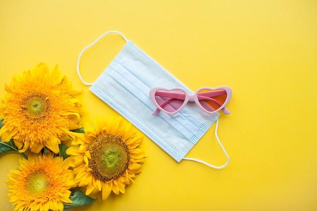 밝은 분홍색 하트 모양의 해바라기 모양의 선글라스와 보호용 의료 마스크의 배열