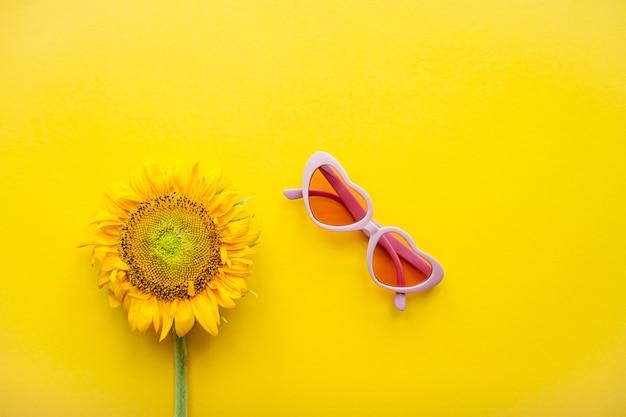 밝은 노란색 배경에 하트와 해바라기 모양의 분홍색 선글라스 배열