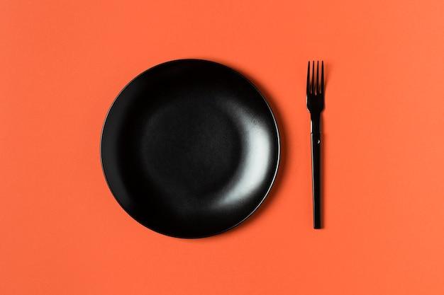 オレンジ色の背景に皿とフォークの配置