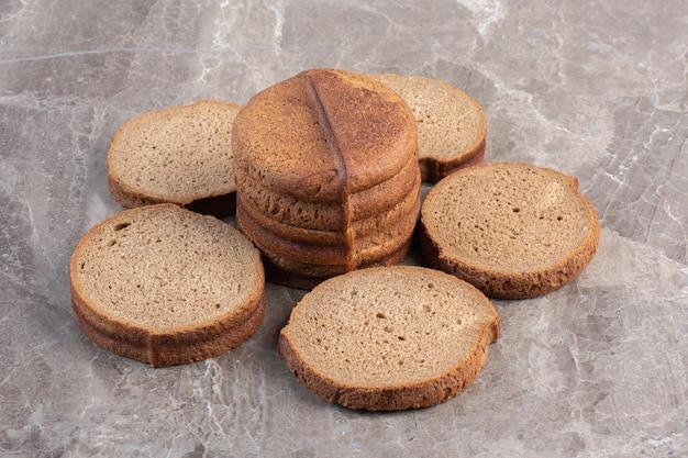 대리석 배경에 검은 빵 조각 배열. 고품질 사진