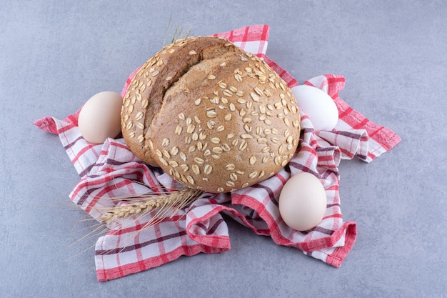 대리석 표면에 수건에 밀 줄기, 계란 및 빵 한 덩어리 배열