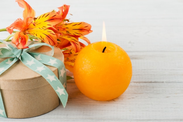 Arrangement of orange lily flowers and candle, gift box