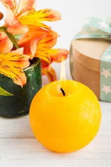 Arrangement of orange lily flowers in green pot, gift box