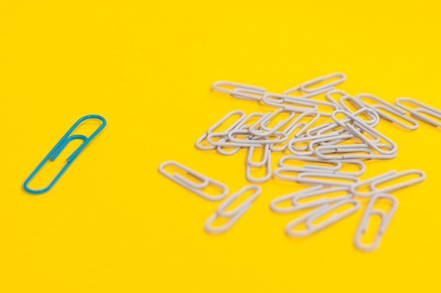 Arrangement of paper clips for individuality concept with one green paper clip