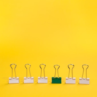 Arrangement of paper clips with one green paper clip