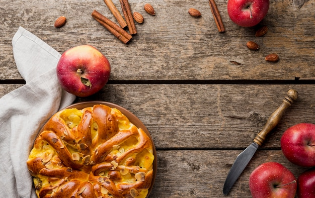 Arrangement of pie and apples with copy space background top view