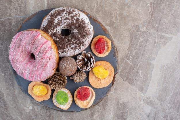 Disposizione di pigne, ciambelle e biscotti su una tavola in marmo.