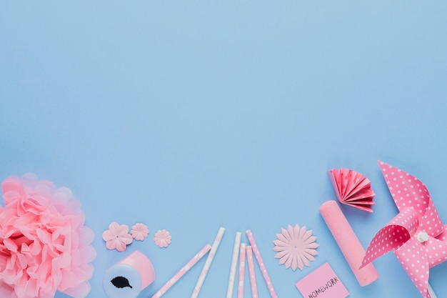 Arrangement of pink craft art and equipment on blue backdrop
