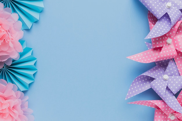 Arrangement of pinwheel and beautiful flower cutout over blue background
