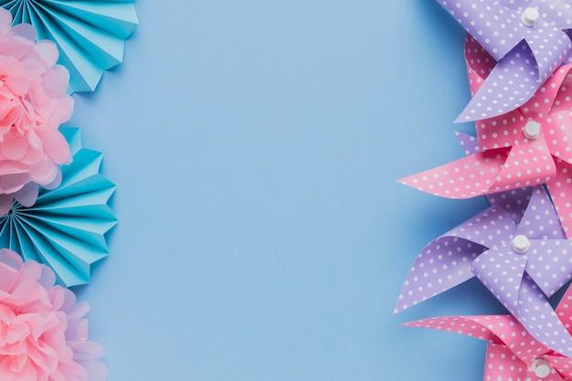Arrangement of pinwheel and beautiful flower cutout over blue background