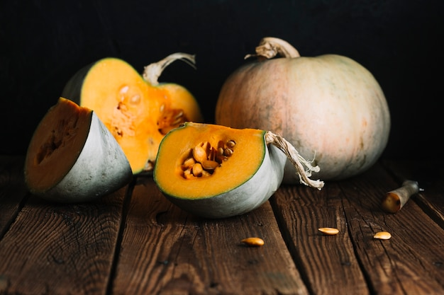 Arrangement of pumpkins and slices on wooden background