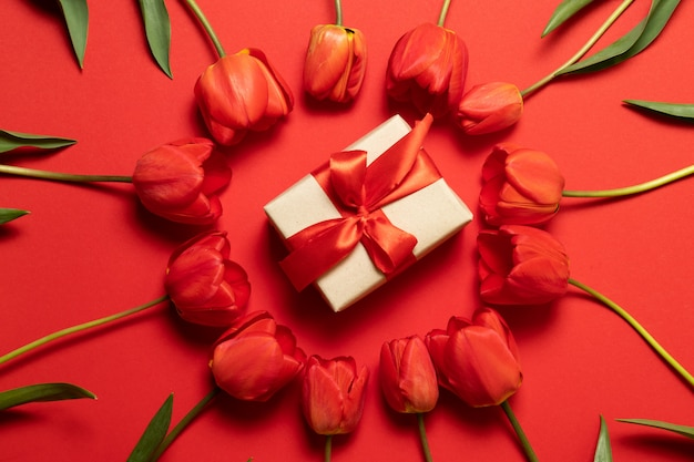 Arrangement of red tulips and a small gift box in the center on red table, top view