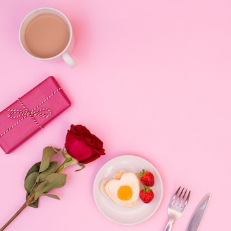 Arrangement of romantic breakfast with rose and present