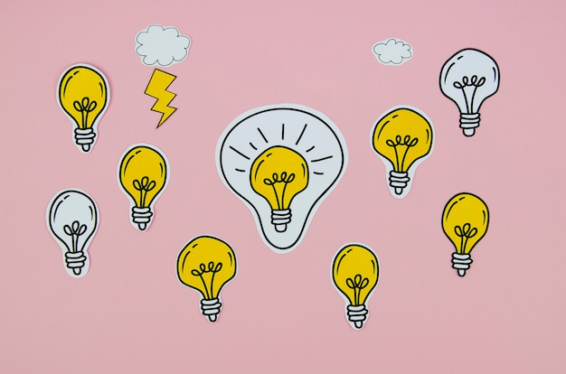 Arrangement of silver and golden light bulbs on pink background