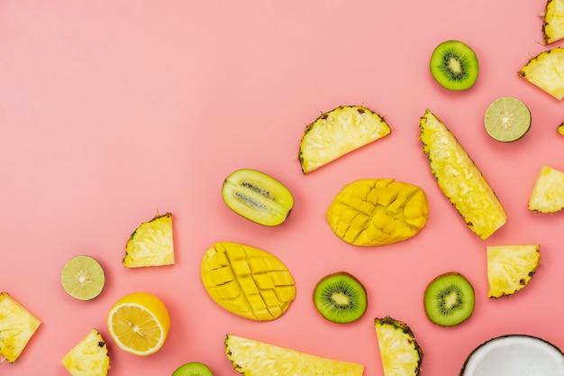 Arrangement sliced various pineapple kiwi mango lemon and lime coconut on pink paper.