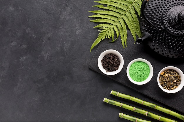 Arrangement of small bowl of herbal tea with fern leaves and bamboo stick