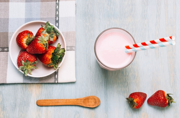 Arrangement of strawberries and smoothie with straws