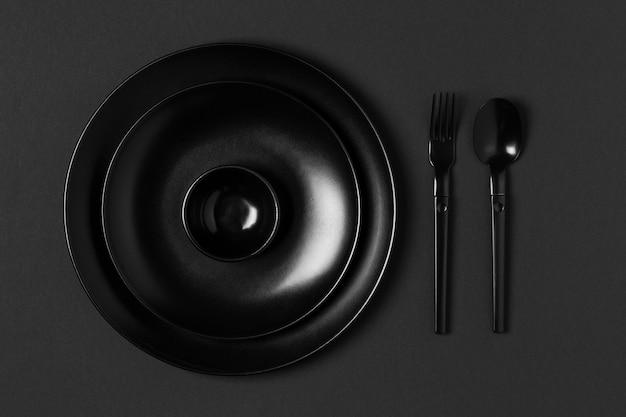 Arrangement of tableware on black background