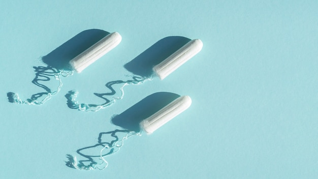 Arrangement of tampons on blue background with shadows