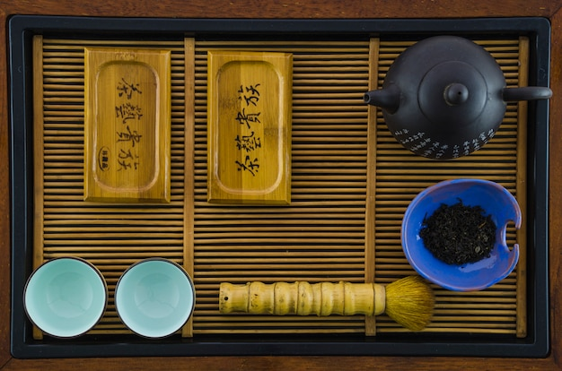 An arrangement of a tea pot; cups; brush; herbs on wooden tray
