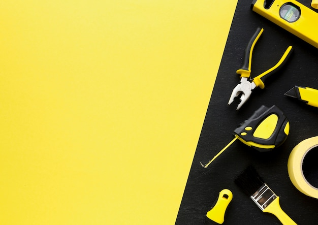 Arrangement of tools with yellow copy space background