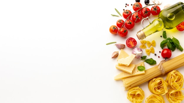 Arrangement of uncooked pasta and ingredients with copy space