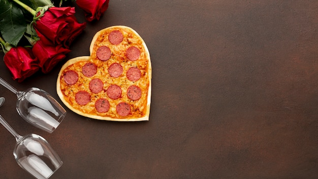 Arrangement for valentines day with heart shaped pizza and copy space