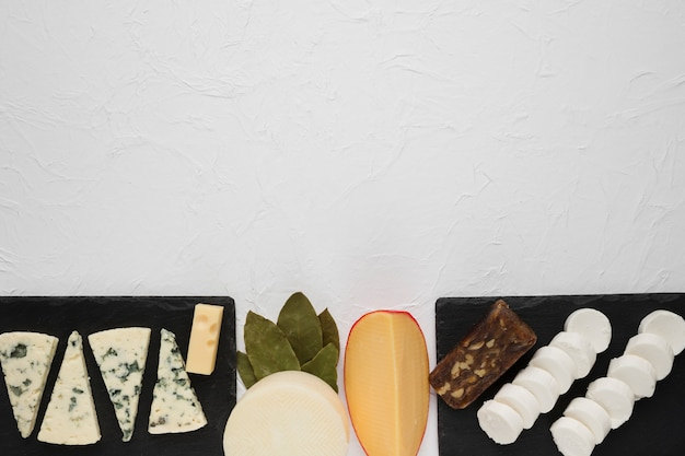 Arrangement of various cheese on black slate with bay leaves at corner of the white surface