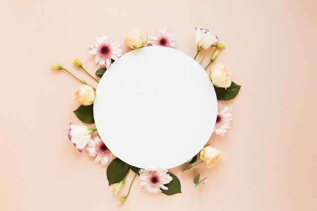 Arrangement of various spring flowers and empty round piece of paper