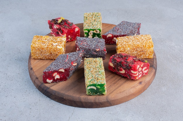 An arrangement of various turkish delight flavors on a wooden board on marble background.