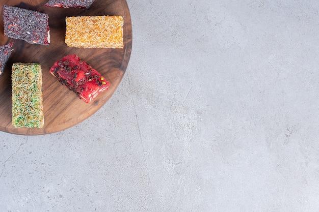 Una disposizione di vari sapori di delizie turche su una tavola di legno su sfondo di marmo.