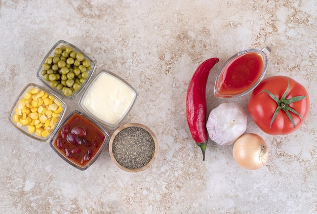 Arrangement of vegetables, dressings, seasoning and toppings on marble surface.