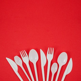 Arrangement of white plastic cutlery on bright red background