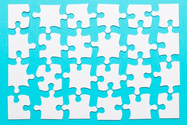 Arrangement of white puzzle piece over blue background