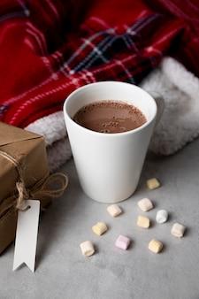 Disposizione degli elementi hygge invernali con una tazza di cioccolata calda