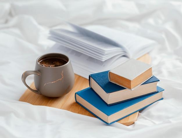 침대에 책과 컵 배치