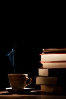 책, 컵 및 어두운 배경 배치