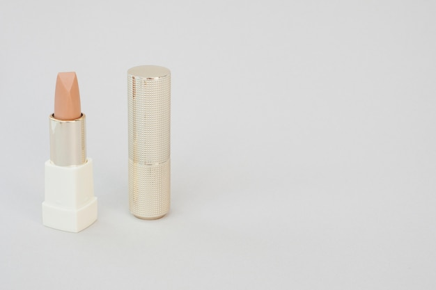 Arrangement with brown lipstick and white background