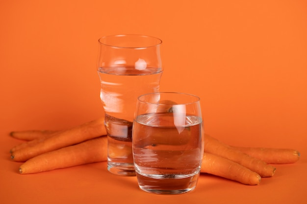 Arrangement with carrots and glasses of water
