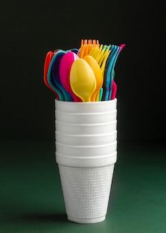 Disposizione con tazze e posate colorate