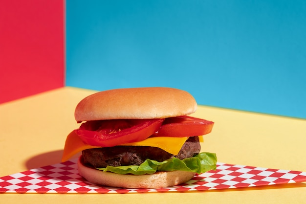 Arrangement with delicious cheeseburger on yellow table