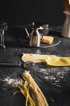 黒いテーブルの上のスパゲッティの生地の配置