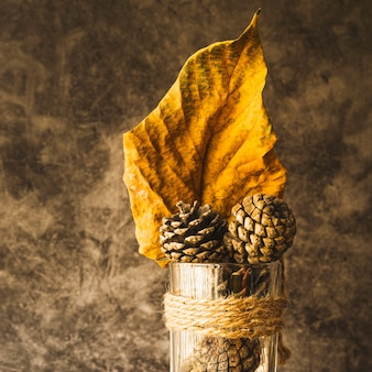 Arrangement with dried yellow leaf and cones
