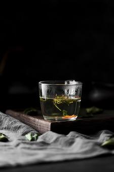 Композиция с напитком с травами и темным фоном