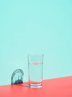 Arrangement with glass of water near blue wall