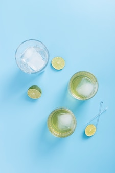 Arrangement with glasses of lemonade and ice cubes